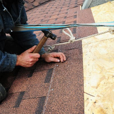 Worker installs bitumen roof shingles with safety equipment